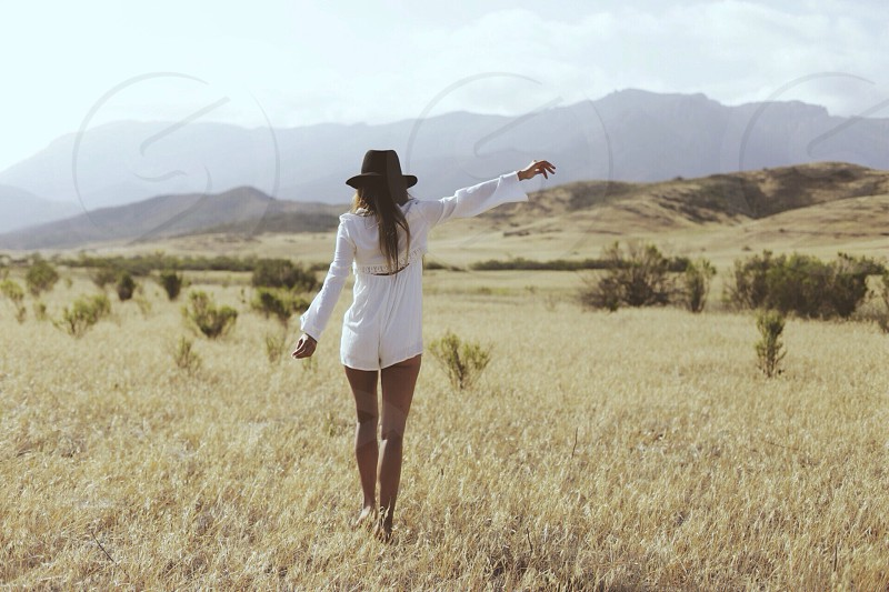 woman in white outfit walking through a grassy field photo