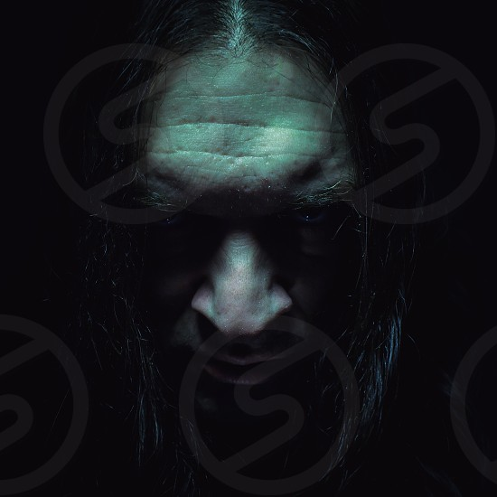 Studio portrait in dark ambient of a man wearing hood and smiling.  photo