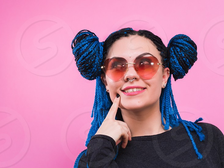 portrait of beautiful young woman in glasses wondering on the wonderful pink studio background. photo