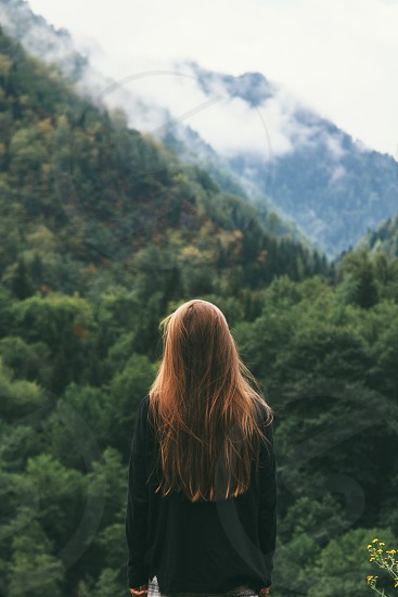 woman in black pullover facing green trees on mountaintop photo