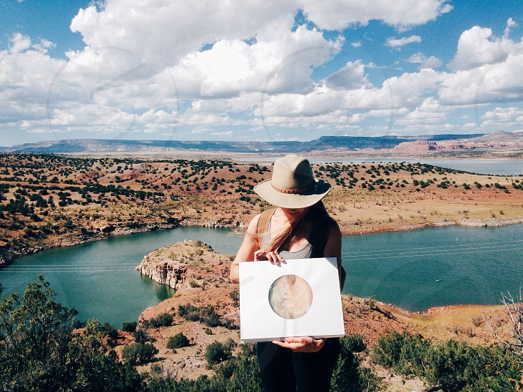 woman in gray tank top and brown western hat holding white box photo