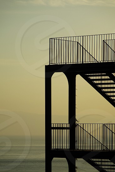 Silhouette of a fire escape with the the sea a a hazy yellowing sky in the background... photo