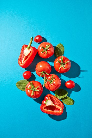Red pepper halves juicy tomatoes and spinach leaves with shadow reflection on a blue background with copy space. Healthy vegetables for salad. Flat lay photo
