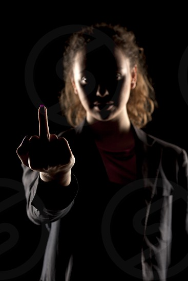 portrait of a girl with the face in a shadow showing middle finger photo