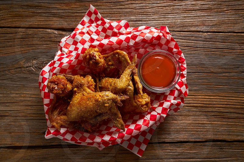 Fried chicken with sauce and spices on wooden table photo