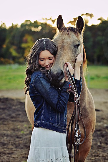 woman in blue denim jacket hugging brown horse photo