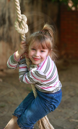 girl in pink grey and white stripe sweatshirt and blue denim pedal pants holding beige rope and smiling during daytime photo