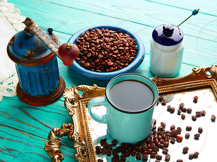 Coffee cup with vintage grinder on wooden old table and golden tray beans photo