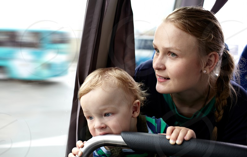 Young mother with her 16 month-old babyboy is traveling by bus. photo