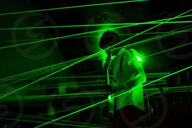 a man playing guitar among green laser light photo