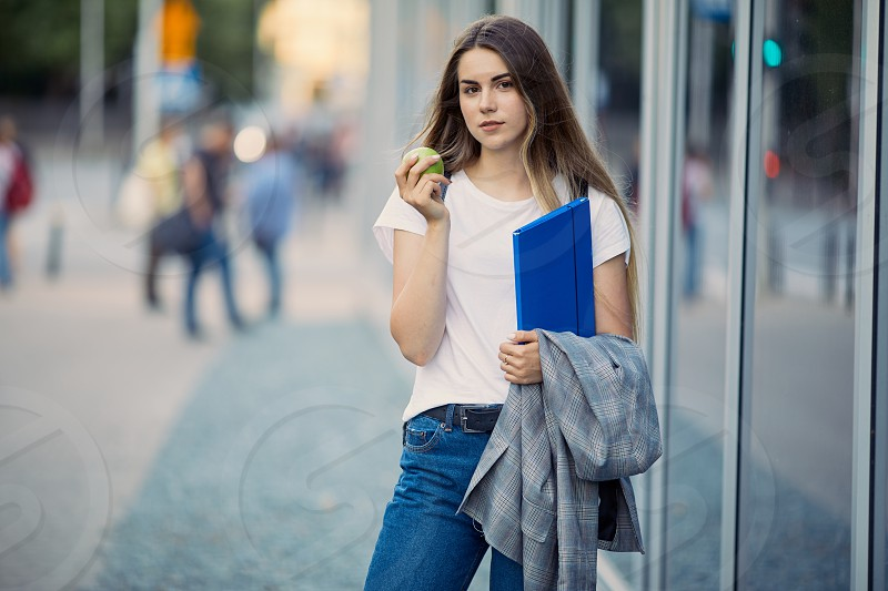 Pretty girl with her blue book on the city street photo