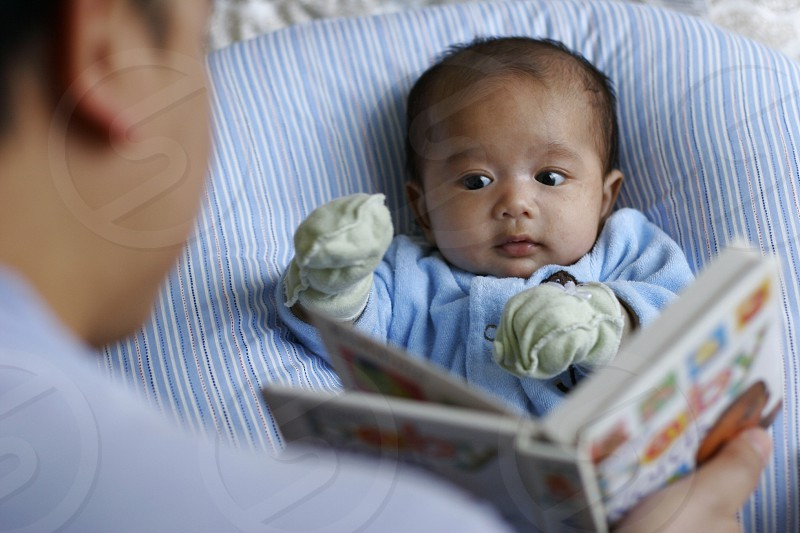 person showing picture book to baby with mitts on photo