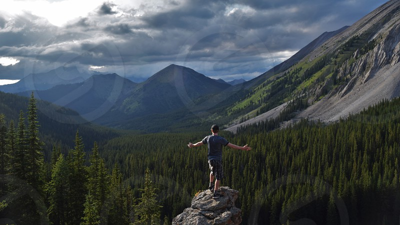 Standing over a beautiful mountain valley taking in the surroundings and becoming one with nature photo
