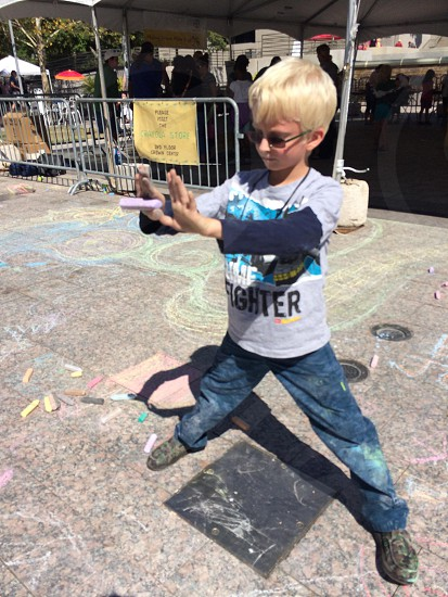 boy dancing in plaza in t shirt and jeans with sidewalk chalk photo