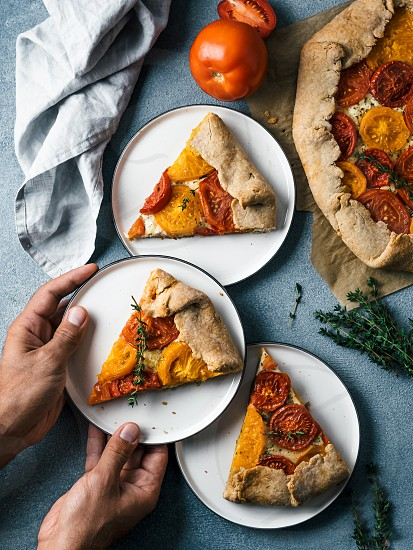 Savory fresh homemade tomato tart or galette.Hands takes piece of pie.Ideas and recipes healthy lunchappetiezer-whole wheat or rye-wheat pie with tomatoescheese.Harvest tomatoes.Top view.Vertical photo
