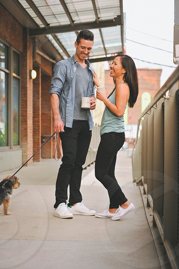 couple with a small dog standing near metal bar fences photo