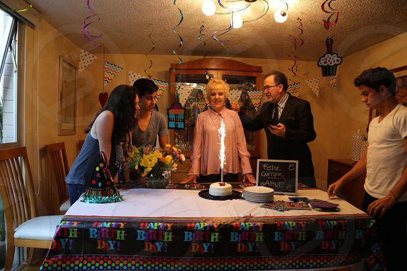 Family celebration birthday grandmother uncle son girl table cake dining room Mexico Mexican  photo