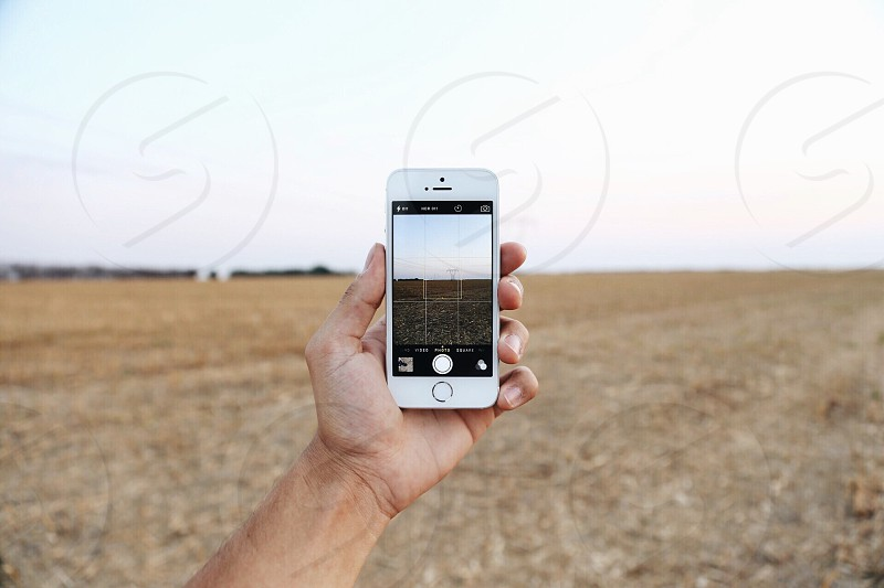 man holding a white iphone taking photo of ground field photo