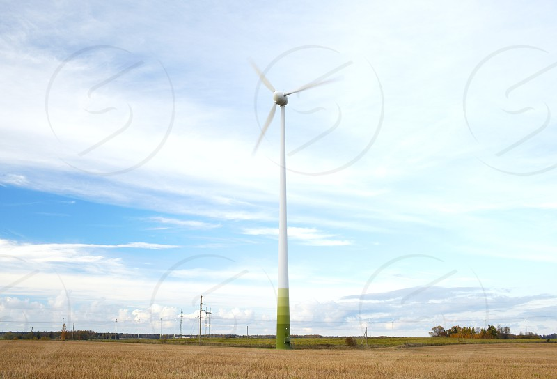 Wind turbine with motion blurred blades over the blue sky with clouds. photo