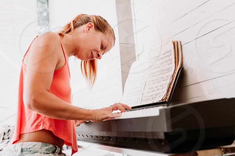Young woman enjoying playing electric piano at home photo