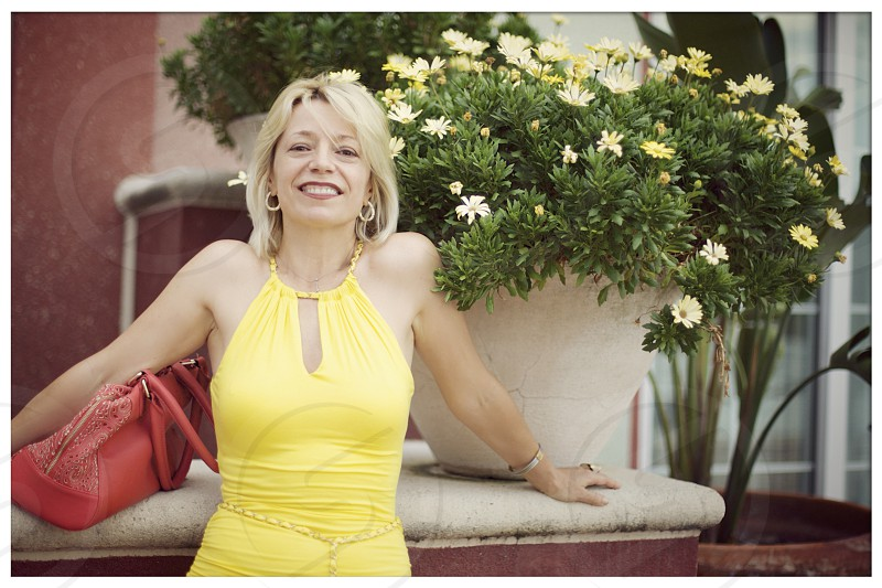 woman wearing yellow halter top standing beside garden vase filled with yellow daisies photo