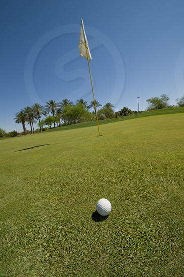 Golf ball on green with flag photo