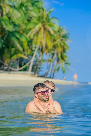 Close-up portrait of a men and his son in water: seven years old cutest blond boy hugged gently his bearded father from the back and give a grimace of happiness. Both in sunglasses photo
