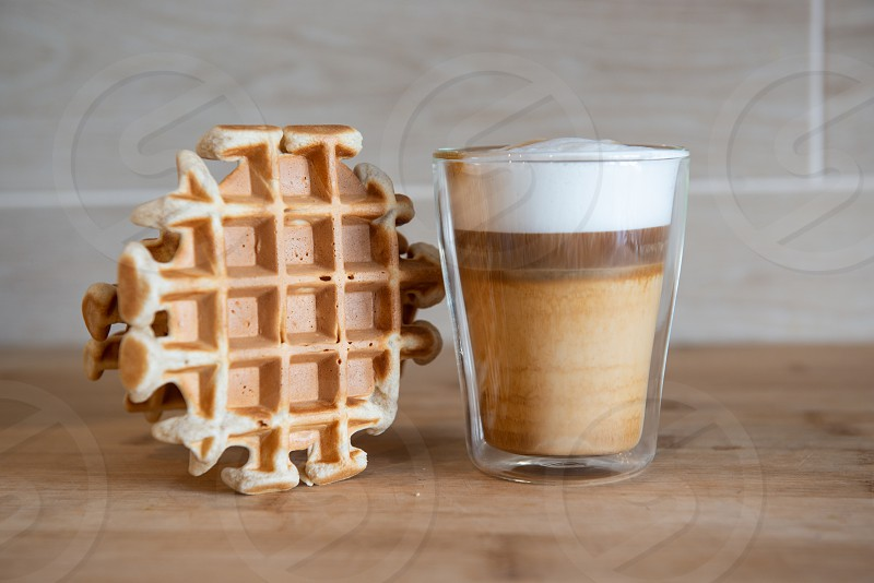 Glass cups of multilayer coffee with mini stroopwafel syrupwaffles cookies on light gray background with copy space. waffle cookies photo