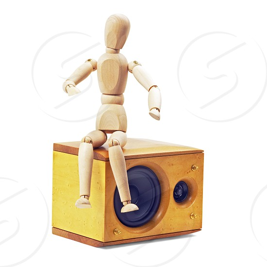wood mannequin sitting on a speaker isolated on white background photo