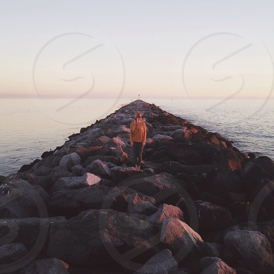 woman standing on black rock path photo