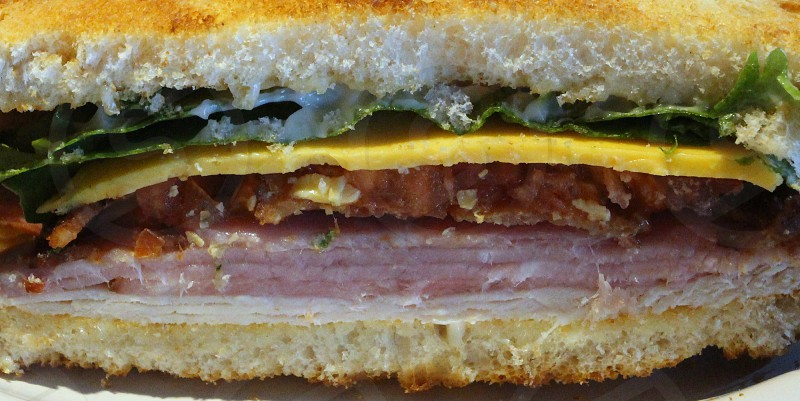 Closeup of cut slice of sandwich with lettuce cheese bacon ham and turkey on white bread photo