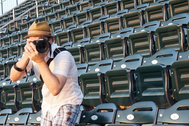 man taking a photo using a black nikon dslr camera photo