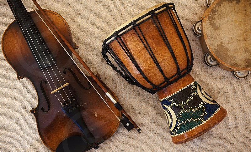 Details of an old and dusty violin from Czechoslovakia djembe and tambourine.  photo