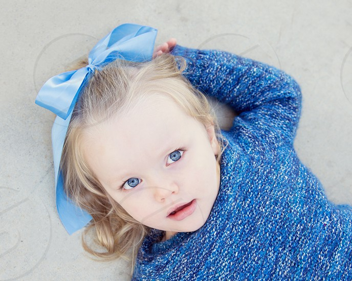 girl wearing blue hairbow and blue knitted sweater photo