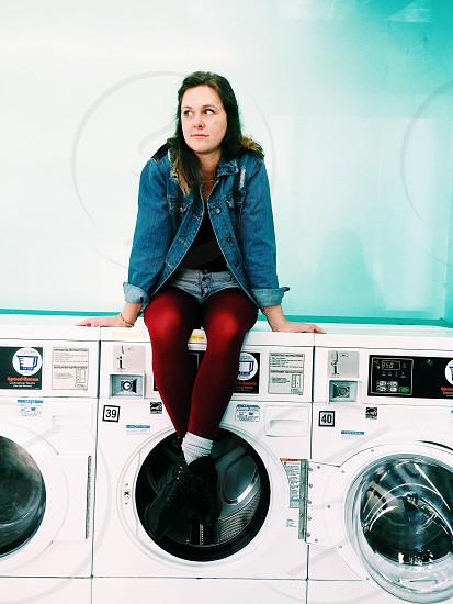 woman in blue denim jacket sitting on front load washing machine photo
