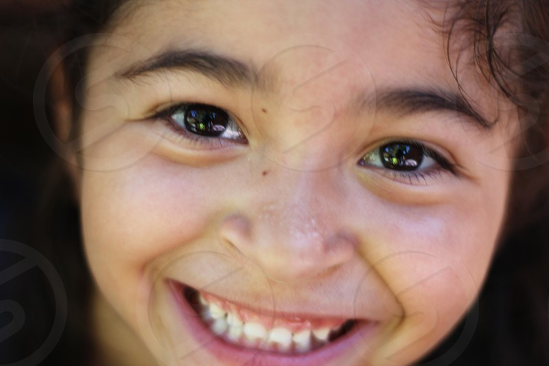 Closeup of girl looking at the camera with a big bright smile photo