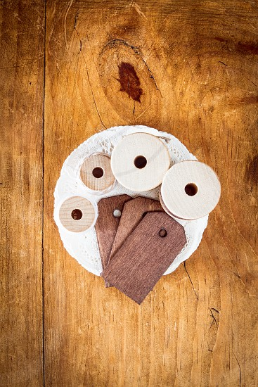 An assortment of spools of thread wooden tags and doilies on a wooden surface. photo