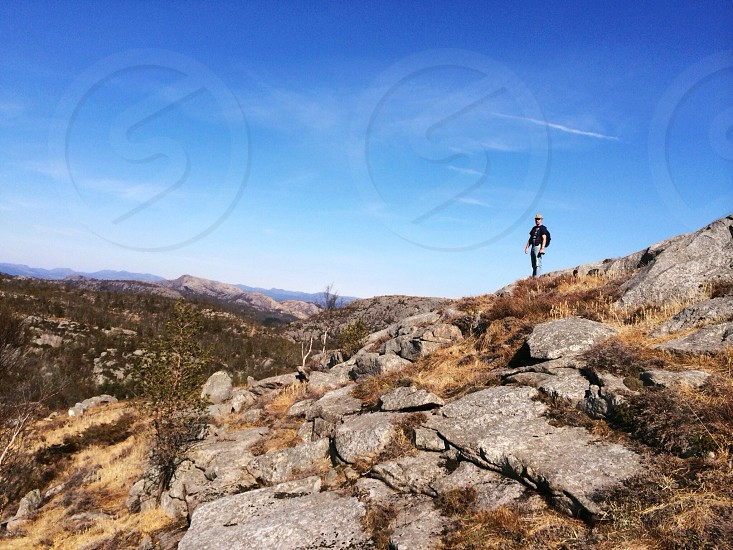 man on top of rocky mountain photo