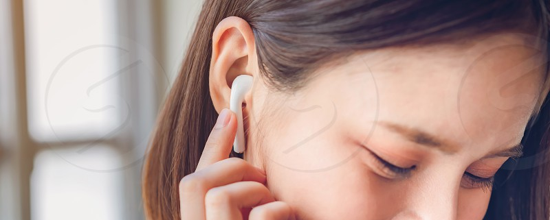 Women are listening to music from white headphones. hands touch to use various functions happy mood. photo