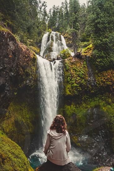 woman in white hoodie sitting on brown rock near cliff watching waterfalls during daytime photo