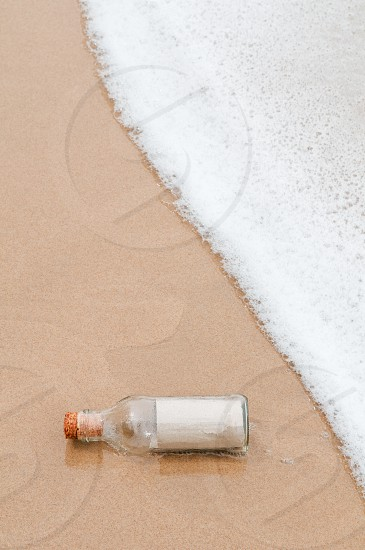 Message in a bottle lying on the beach photo