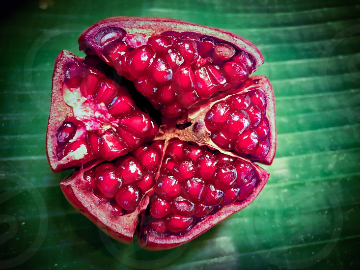 red ripe pomegranate Punica granatum fruit plant tree juicy berry sweet tasty fresh food healthy agriculture organic tropical half sliced seed banana leaf background photo