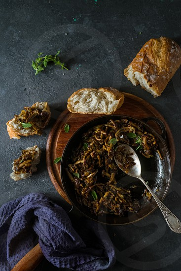 Fried mushrooms in a skillet pieces of bread on a dark rustic background photo