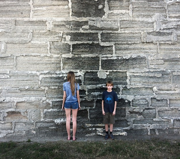 woman and a boy standing near grey wall photo
