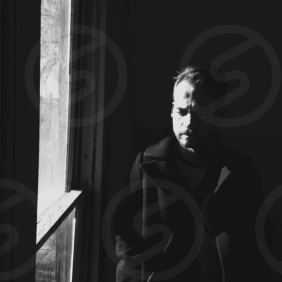 man in black coat standing beside glass window photo