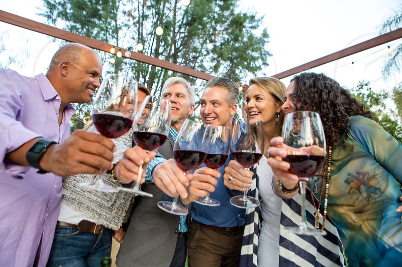 Friends in their forties and fifties Drinking red wine celebrating an Anniversary mixed ethnicity photo