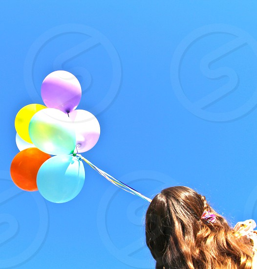 Girl holding balloons photo