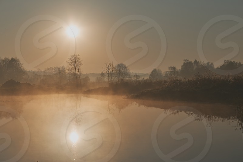 Sun rising above field and pond flooded with fog in the morning photo