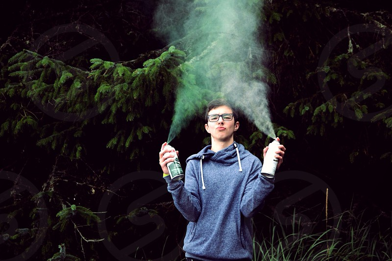 boy in grey hoodie holding spray paint photograph photo