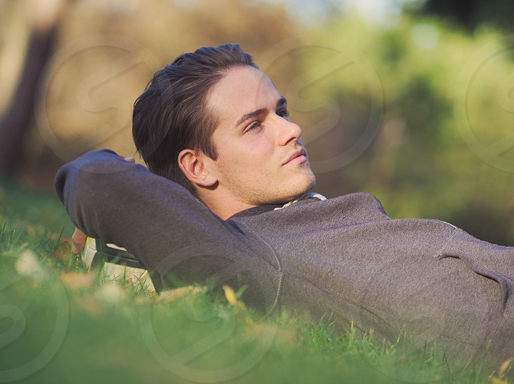 Soccer Player Lying in the Grass with Football in the Park on a Sunny Autumn Day photo